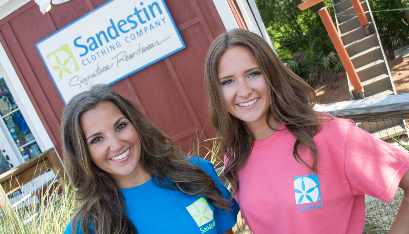 Two women posing outside of Sandestin Clothing Company in branded shirts