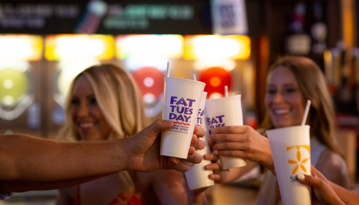 individuals cheersing Fat Tuesday cups