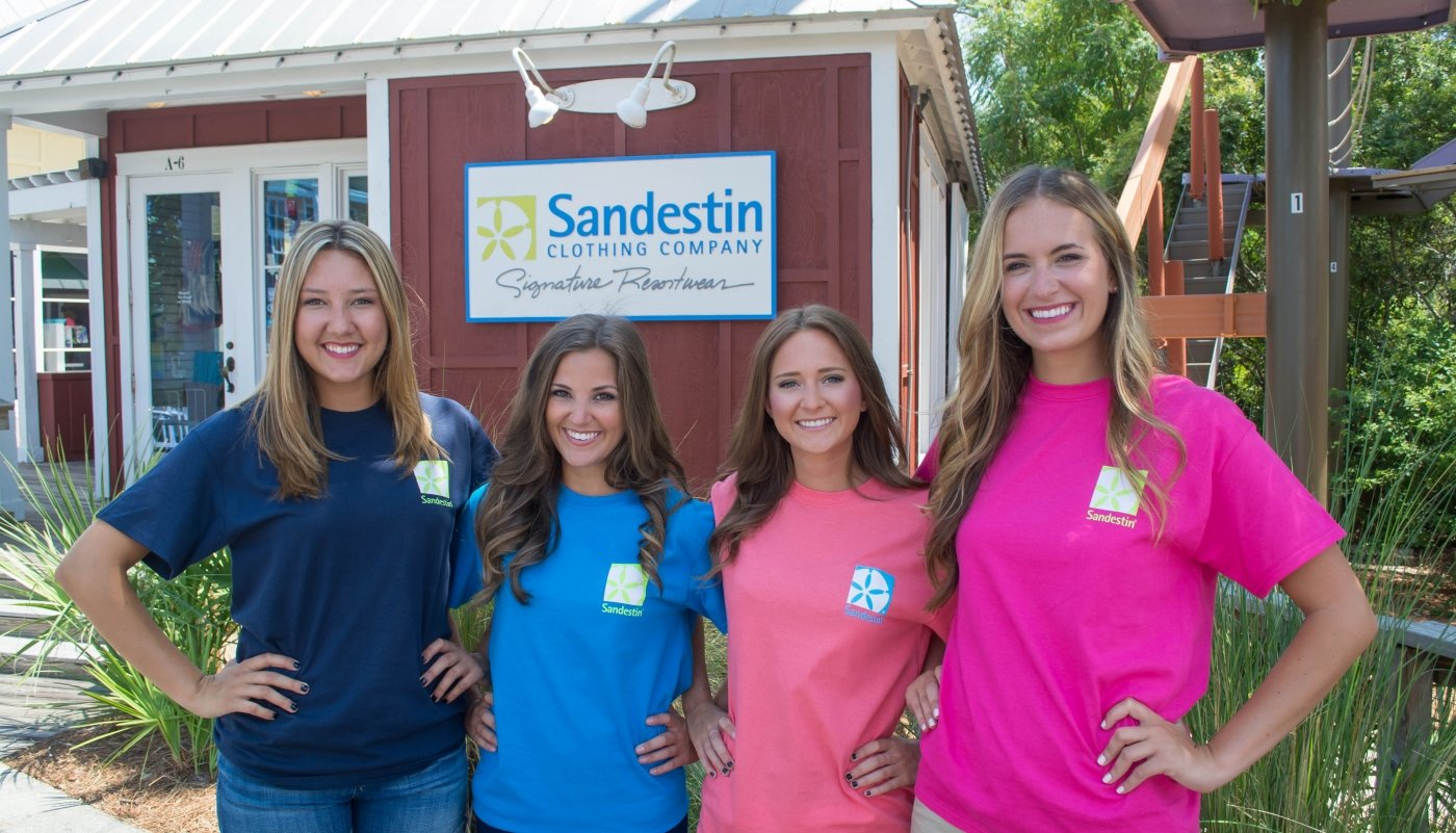 Four women posing outside of the Sandestin Clothing Company store with branded shirts