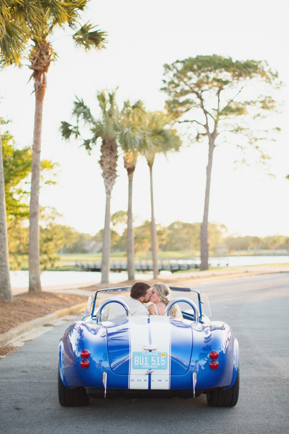 Bride and groom kissing in convertible