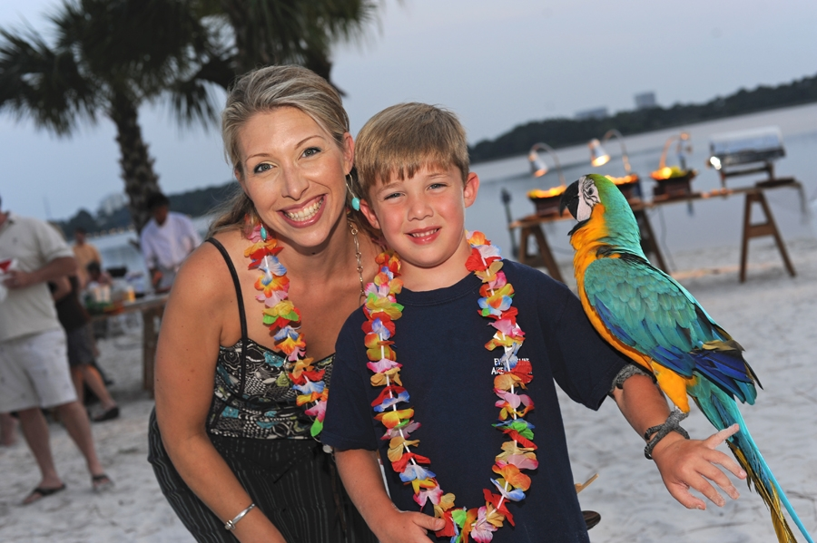 Mother and son posing with a parrot