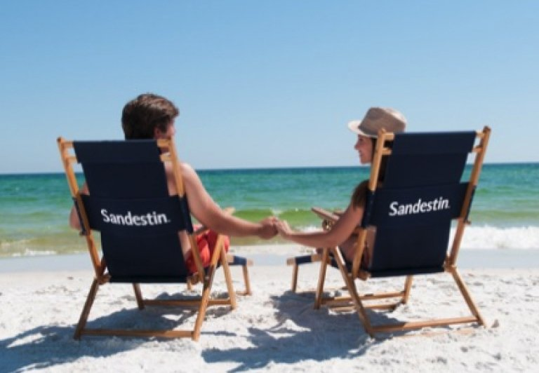 A couple relaxes on the beach in Sandestin beach chairs