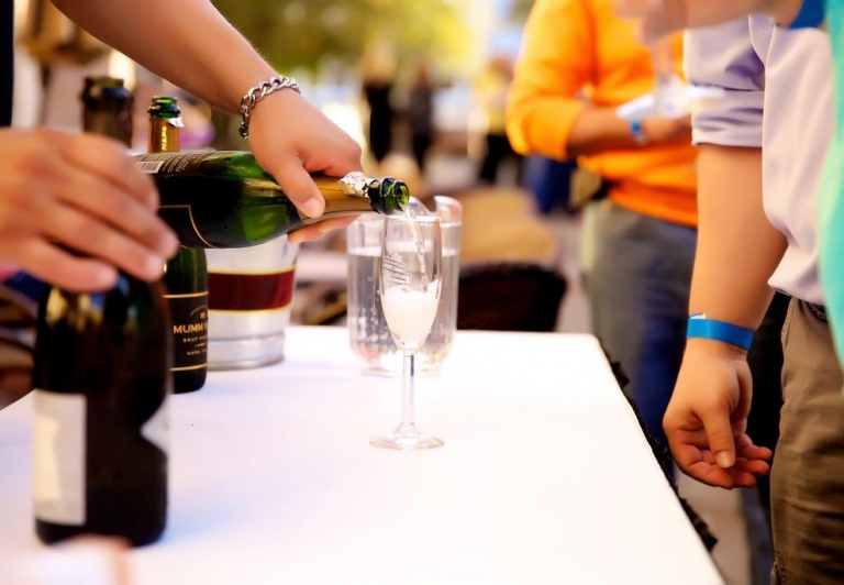 a person pouring a glass of champagne at a public event