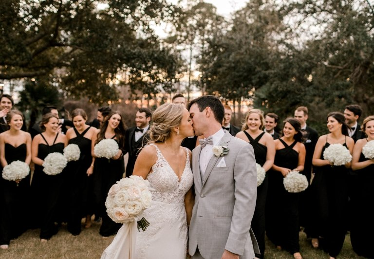 Bride and groom kissing with wedding party standing behind them