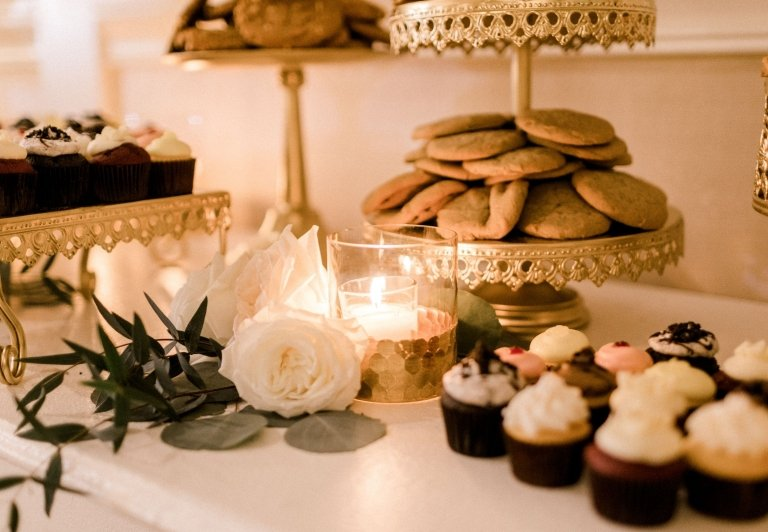 treat table at a wedding reception with flowers, candles and cupcakes
