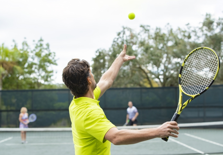 man serving a tennis ball
