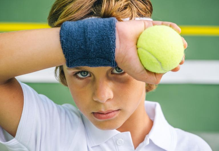 kid wiping his brow playing tennis