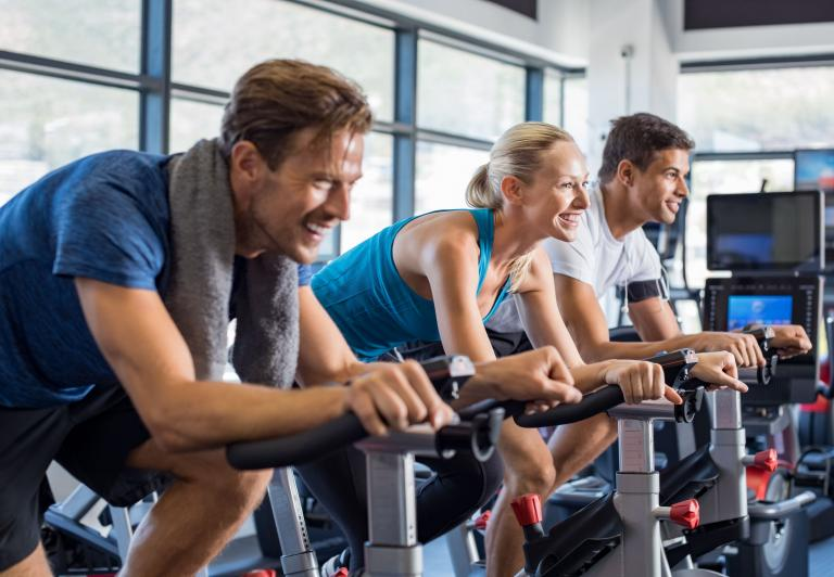men and women in a spin class