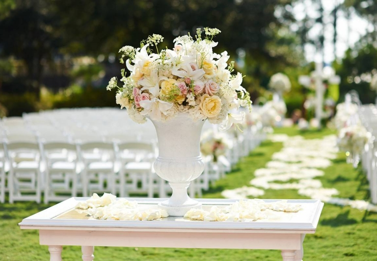outdoor wedding set up with a white table and rows of chairs