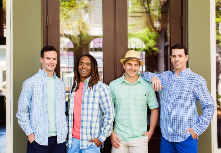 Four men standing outside of Island Clothiers