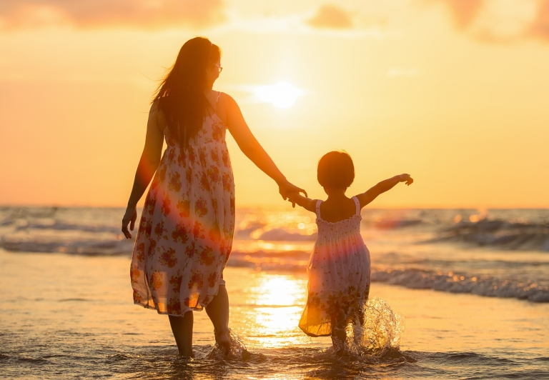 Mother and child walking along the beach with a sunset in the background