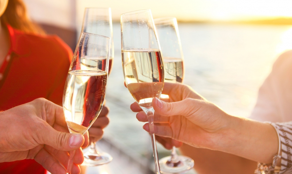 Individuals cheersing glasses f champagne on a dinner cruise