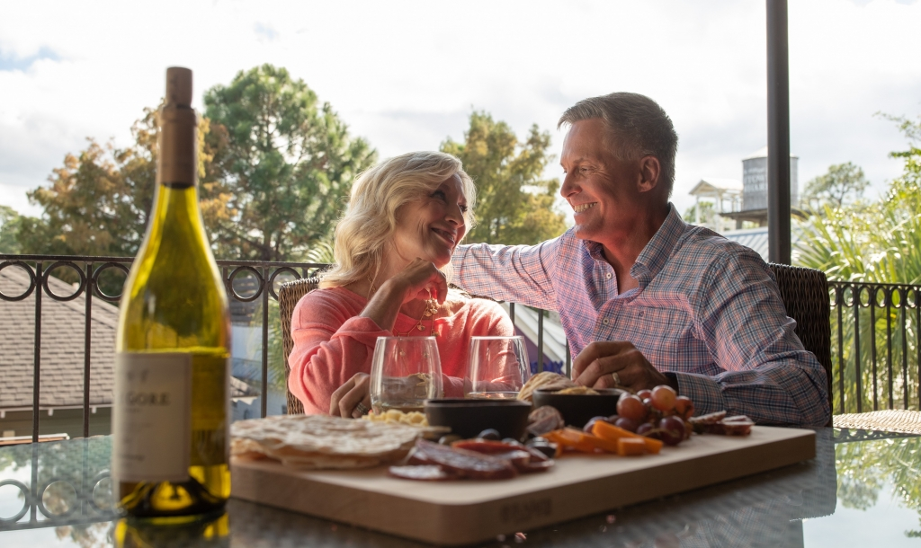 couple enjoys a bottle of wine and charcuterie board on a patio