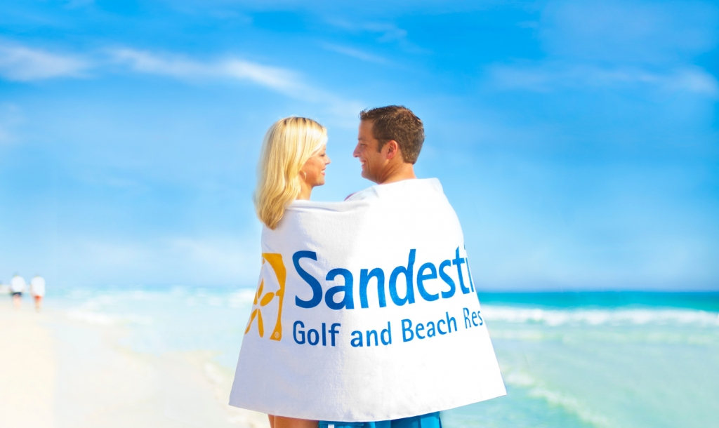 couple on the beach wrapped in a Sandestin towel