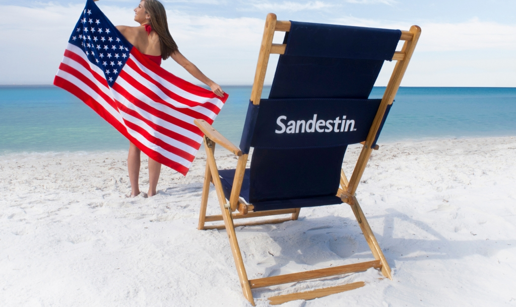 Woman on the beach with an American flag and beach chair