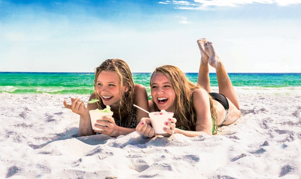 girls laying in the sand eating sno-cones
