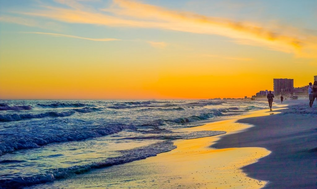 A beach with a golden sunset at Sandestin Golf and Beach resort