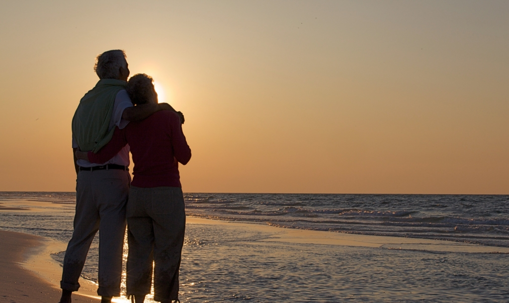 A couple standing on the beach at Sandestin Golf and Beach resort with a beautiful sunset in the background