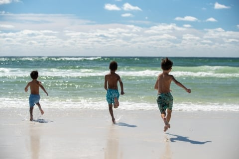 Children running towards the beach