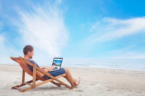 man in beach chair on beach with laptop