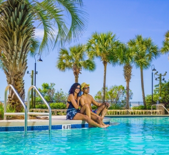 Couple relaxing at the edge of a pool