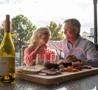 older man and woman enjoying dinner on a patio