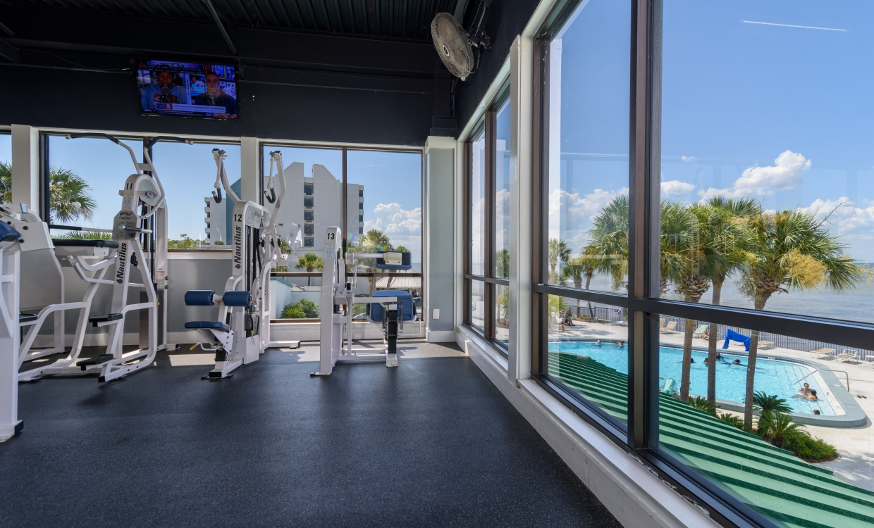 fitness equipment in front of a large window overlooking a pool
