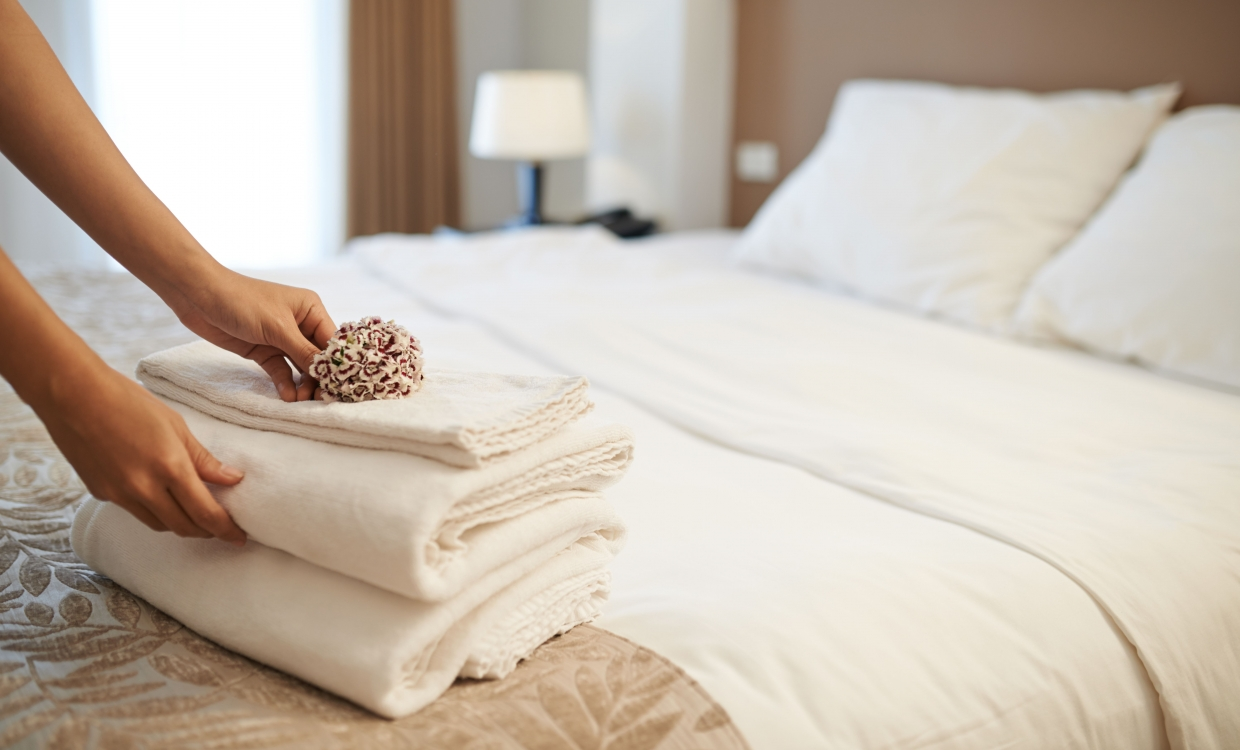 individual putting fresh towels on a bed
